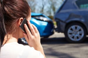 Female Driver Making Phone Call After Traffic Accident, looking at the accident